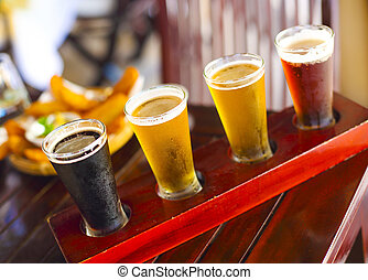 Four sorts of beer. Beer tasting. Ale, porter, lager, pilsner
