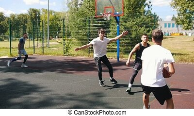 Four sportsmen playing basketball on the court outdoors -...