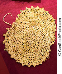 Four straw trivets on a red background