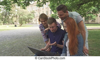 Four students laugh at what they see on laptop on campus