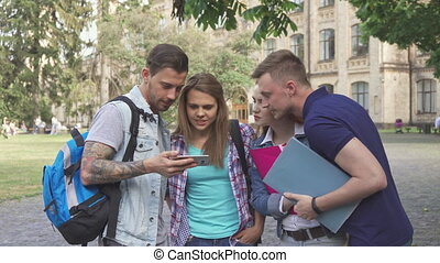 Four students look at smartphone screen on campus