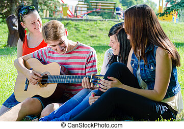 Four teen friends playing guitar - Group of happy teen...