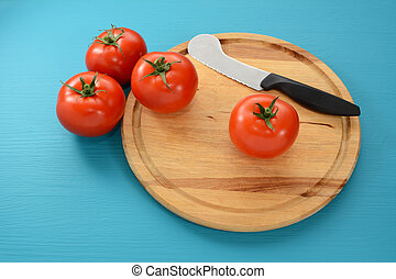 Four tomatoes on a chopping board with a knife