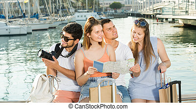 Four traveling young people searching for direction using paper map on waterfront in town