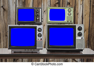 Four Vintage Televisions With Chroma Key Blue Screens and Old Wood Wall