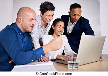four well dressed individuals working together on one notebook