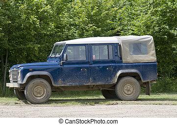 A four wheel drive truck on a farm track