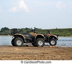 A pair of quad bikes on sandy riverside