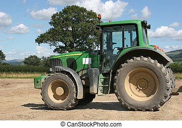 Green four wheel drive tractor standing idle on rough ground, with rural countryside to the rear and a blue sky with cumulus clouds.