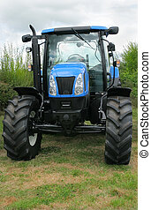 New blue and black four wheel drive tractor standing idle in a field.