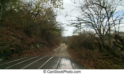 Four-wheel drive vehicle on stony track in mountains of...