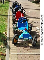 Derelict children's four-wheeled bikes. Path of park.