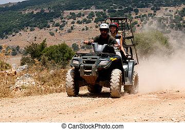 A four-wheeler ATV runs through trail on sunny day