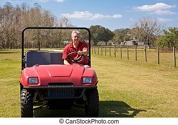Farmer driving an all terrain vehicle over his property.