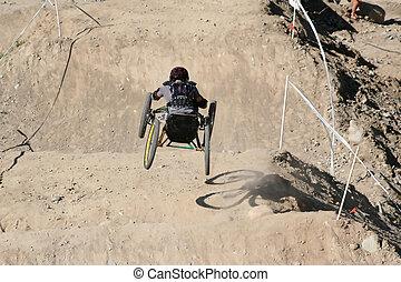 A paraplegic racer flies down the hill on his custom made four wheeled bike.