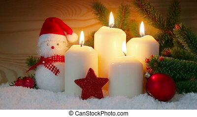 Four white Advent candles burning and Snowman . - Four white...