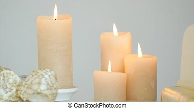Four white candles burning on white