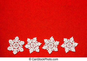 Four white crochet snowflakes in a row on red felt ...