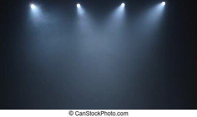 Four white spotlights illuminate dark smoky concert hall of...