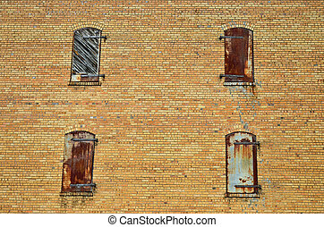 Four windows in an old building: three have metal shutters ...