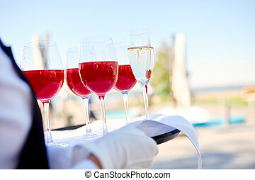 four wine glasses with red alcoholic drink and one glass of champagne on a tray of the waiter