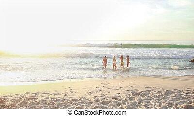 Four women walking up the beach