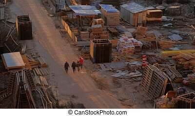 Four workers are walking along a dusty road to the construction site