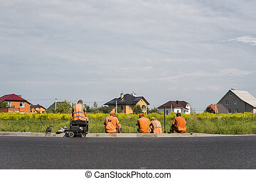 Four workers resting on the road construction site with a houses behind them.