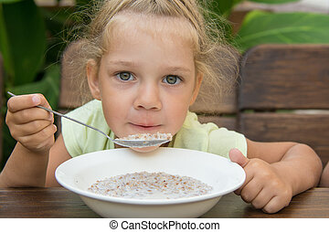 Four-year-girl at the table in the fresh air blowing on a spoonful of porridge
