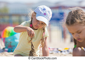 Four-year girl builds a sand castle on the beach