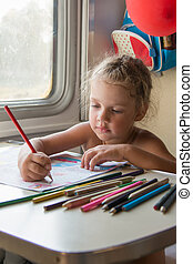 Four-year girl drawing with pencils at a table in a train