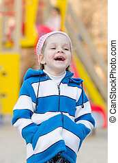 Four-year girl laughing in the playground