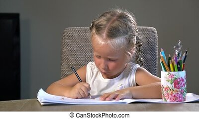 four-year girl performs educational tasks sitting at the...