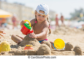 Four-year girl playing in the sand on beach seaside