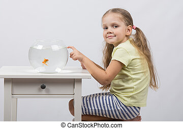Four-year girl sitting in front of an aquarium with goldfish and knocks his finger on it