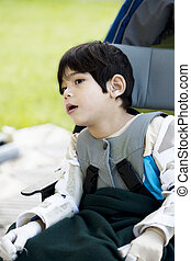 Four year old boy disabled with cerebral palsy sitting outdoors in wheelchair