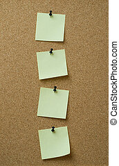 four yellow notes pinned to cork background