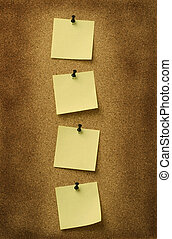 four yellow notes pinned to grunge cork background