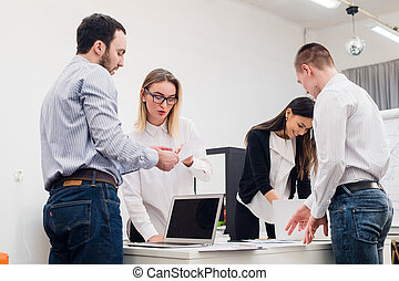 Four young business people working as a team gathered around laptop computer in an open plan modern office