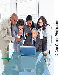 Four young executives attentively looking at the laptop screen