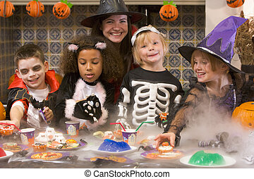 Four young friends and a woman at Halloween eating treats ...