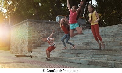 Four young friends, schoolchildren jumping from the stairs...
