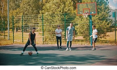Four young men playing basketball on the sports ground