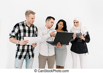 Four young multiethnical people, African and Muslim girls, two Caucasian men, holding papers and different gadgets standing near light white wall. Education, business concept