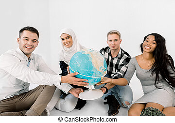 Four young multiracial people holding hands and hug Earth globe, sitting on the floor, on the white background. Save the Planet, Earth day concept.