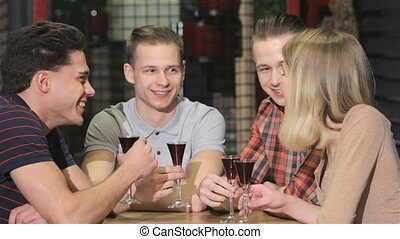 Four young people drink liquor at the bar