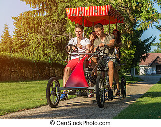 four young people in a four-wheeled bicycle
