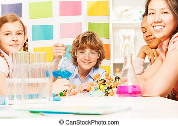 Four young students doing a chemistry experiment