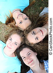 Four young teenage girls looking up at the camera