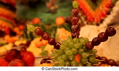 Fourchette sweet table with fruit on a background of colorful tapestry